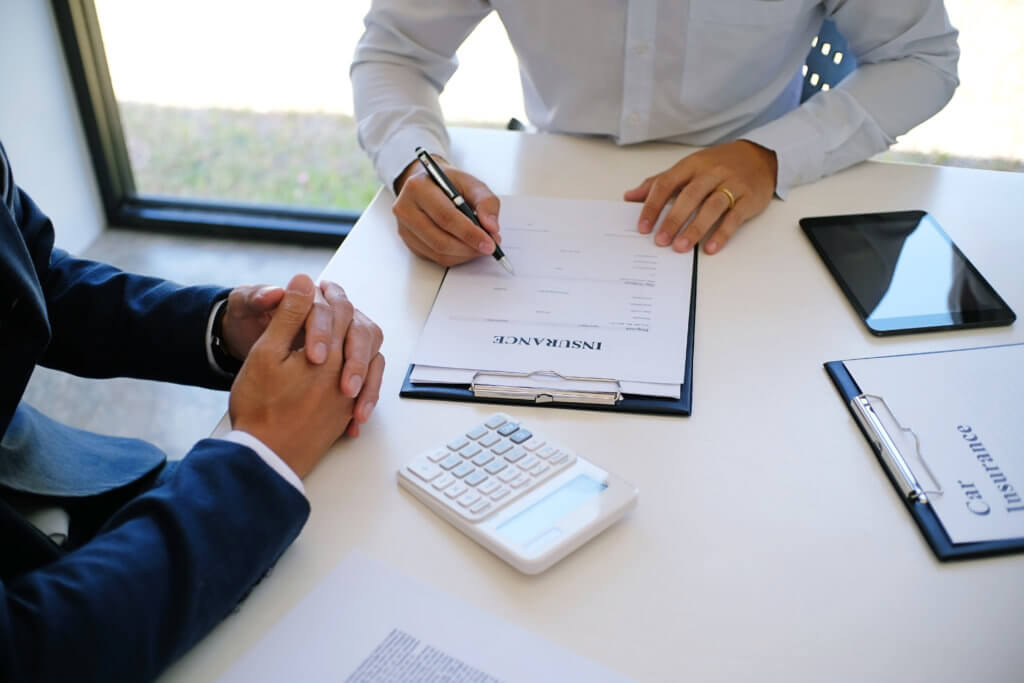 Sales manager giving advice application form document, considering mortgage loan offer for car insurance