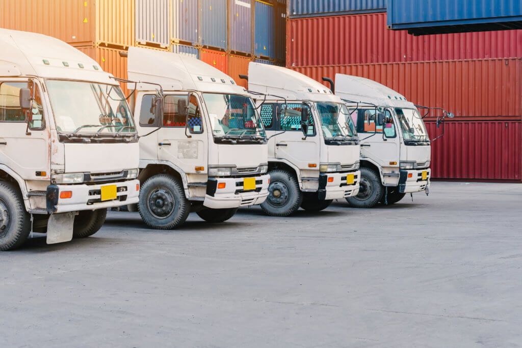 Line of cargo truck with container box for export import shipping at yard. transport concept
