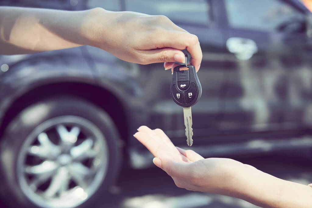 Woman's hand give the car key, rent a car concept