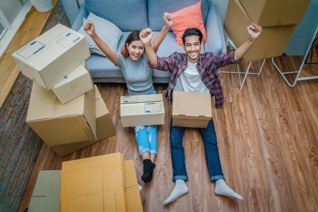 Top view Asian young couple are glad after successfull packing the cardboard box for moving in new house, Helping relocate and joshing together, Moving and House Hunting concept, selective focus