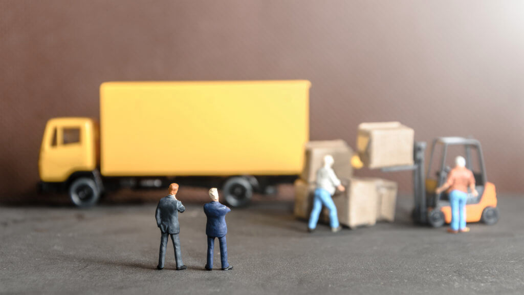 miniature business man looking at workers carrying products goods box to container truck in distribution warehouse factory. logistics warehouse freight transportation concept