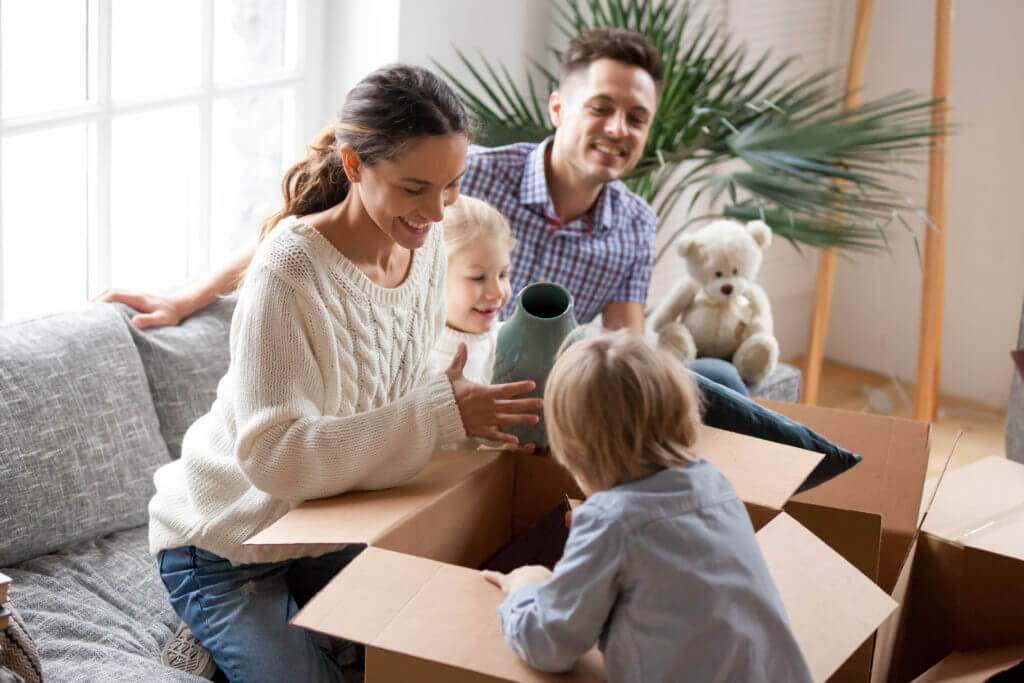 Happy family with two kids unpacking boxes after relocation moving into or settling in new home concept, excited small children helping parents with belongings sitting on sofa in living room together